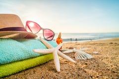 太阳镜、毛巾、帽子、太阳块、壳和海星在含沙 图库摄影