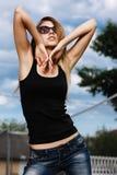 太阳镜、黑T恤杉和牛仔裤的美丽的金发碧眼的女人 免版税库存照片