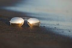 太阳镜反射落日的光在沙滩 免版税库存照片