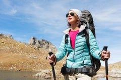 太阳镜和一个帽子的一个远足者女孩有有跟踪的艰苦跋涉的一个背包和山齿轮的在她的手上看 免版税库存图片