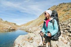 太阳镜和一个帽子的一个远足者女孩有有跟踪的艰苦跋涉的一个背包和山齿轮的在她的手上看 库存图片