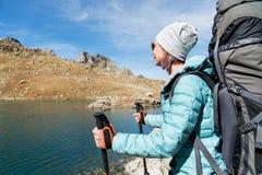 太阳镜和一个帽子的一个远足者女孩有有跟踪的艰苦跋涉的一个背包和山齿轮的在她的手上看 免版税库存照片