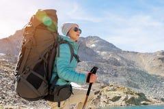 太阳镜和一个帽子的一个远足者女孩有有跟踪的艰苦跋涉的一个背包和山齿轮的在她的手上看 免版税图库摄影