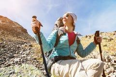 太阳镜和一个帽子的一个远足者女孩有有跟踪的艰苦跋涉的一个背包和山齿轮的在她的手上看 库存照片