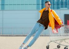 太阳镜和一个救生服的时尚人在从食物的一个推车坐在超级市场停车处 库存图片