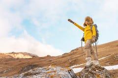 太阳镜和一顶大北裘皮帽的背包徒步旅行者女孩有在她的一个背包的回来在岩石和看的点 免版税库存图片