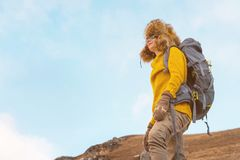 太阳镜和一顶大北裘皮帽的背包徒步旅行者女孩有在她的一个背包的在岩石站立和 免版税库存图片