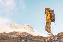 太阳镜和一顶大北裘皮帽的背包徒步旅行者女孩有在她的一个背包的在岩石站立和 免版税图库摄影