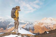 太阳镜和一顶大北裘皮帽的背包徒步旅行者女孩有在她的一个背包的在岩石站立和 库存照片