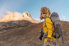 太阳镜和一顶大北裘皮帽的背包徒步旅行者女孩有在她的一个背包的在岩石站立和 库存图片