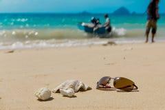 太阳镜和壳在热带海滩与离去的小船 免版税库存图片
