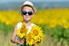 太阳镜和帽子的可爱的男孩用在户外领域的向日葵 免版税库存照片