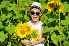 太阳镜和帽子的可爱的笑的白肤金发的男孩用在领域的向日葵户外 库存照片