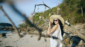 太阳镜和帽子的年轻性感的妇女微笑和摆在树附近的在美丽的热带海滩 免版税库存照片