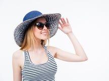 太阳镜和帽子的愉快的逗人喜爱的妇女 免版税库存照片
