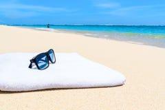 太阳镜和毛巾在热带白色沙滩 免版税库存图片