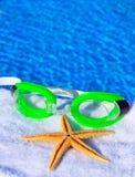 太阳镜和海星在毛巾 免版税库存照片