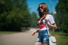 太阳镜和牛仔布短裤的一个可爱的女孩在公园等待 免版税库存图片