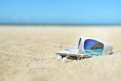 太阳镜和电话在海滩 免版税库存图片