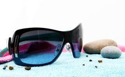 太阳镜和石头在海滩毛巾 图库摄影