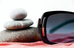 太阳镜和禅宗石头在海滩毛巾 免版税库存图片