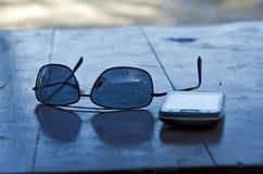 太阳镜和移动电话 免版税库存照片