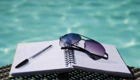 太阳镜和笔在笔记薄 库存图片