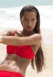 太阳镜和红色比基尼泳装的美丽的妇女在海滩 塑造查找 性感的夫人 免版税库存图片