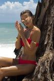 太阳镜和红色比基尼泳装的美丽的妇女在海滩 塑造查找 性感的夫人 库存照片
