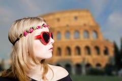 太阳镜和花圈的女孩在被弄脏的大剧场 免版税库存图片