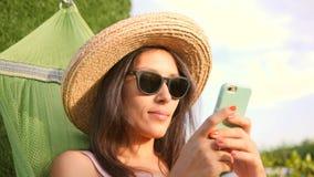 太阳镜和草帽的年轻混合的族种旅游女孩使用在吊床的手机在自然日落的公园 影视素材