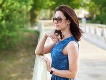 太阳镜和蓝色牛仔裤礼服的可爱的深色的妇女安排在手机的情感电话交谈在公园桥梁胜过 免版税库存图片