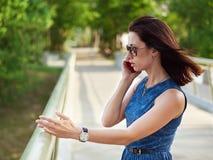 太阳镜和蓝色牛仔裤礼服的可爱的深色的妇女安排在手机的情感电话交谈在公园桥梁胜过 库存照片