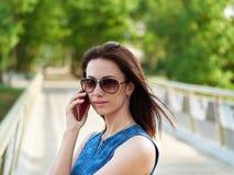 太阳镜和蓝色牛仔裤礼服的可爱的深色的妇女安排在手机的情感电话交谈在公园桥梁胜过 免版税库存照片