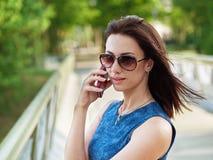 太阳镜和蓝色牛仔裤礼服的可爱的深色的妇女安排在手机的情感电话交谈在公园桥梁胜过 库存图片