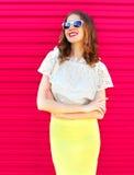 太阳镜和裙子的愉快的俏丽的微笑的妇女在五颜六色的桃红色 免版税库存照片