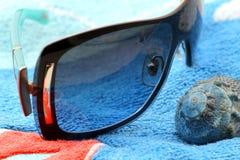 太阳镜和贝壳在海滩毛巾 库存照片