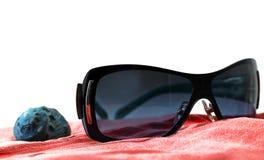 太阳镜和贝壳在红色海滩毛巾 免版税图库摄影
