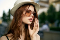 太阳镜和戴的一个帽子年轻美丽的妇女在街道上在城市,画象 库存图片