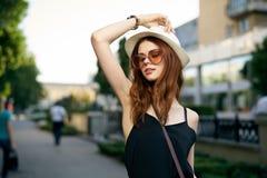 太阳镜和戴的一个帽子年轻美丽的妇女外面在城市 图库摄影