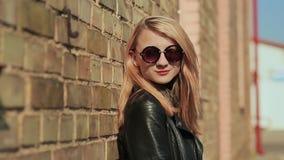太阳镜和黑皮夹克的时髦的年轻金发碧眼的女人在街道上的一个砖墙附近 影视素材