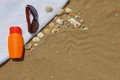 太阳镜和sunblock在beachtowel 库存图片