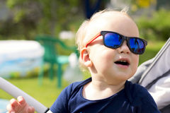 太阳镜坐室外和笑的滑稽的男婴 免版税库存照片