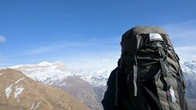 太阳镜帽子的一个有胡子的人有背包和照相机的站立高在山和神色在边线 影视素材
