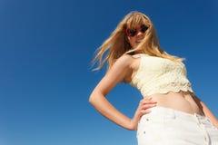 太阳镜放松的女孩室外反对天空 免版税库存照片