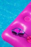 太阳镜桃红色气垫游泳池 热带概念 免版税库存图片