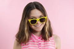 太阳镜的一个十几岁的女孩看照相机和微笑 免版税库存图片