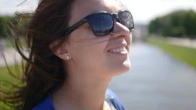 太阳镜的一个女孩支持湖,微笑对近来风 慢的行动 1920x1080 充分的HD 股票视频