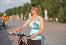 太阳镜的一个少妇站立与在promena的一辆自行车 库存图片