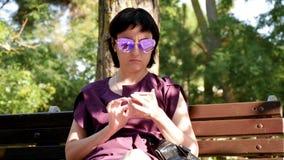 太阳镜的一个深色的女孩坐一条长凳在夏天公园并且使用她的电话 移动通信,应用 股票录像